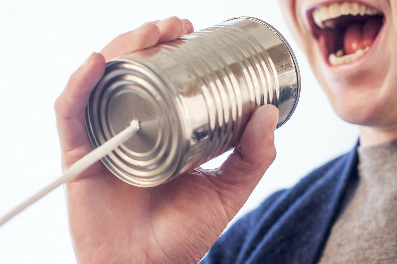 Image of someone holding a can with a string for the telephone game.